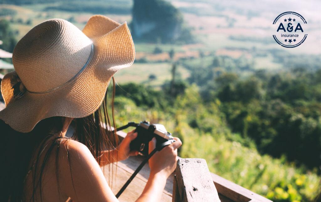 una mujer frente a un paisaje con una cámara en la mano