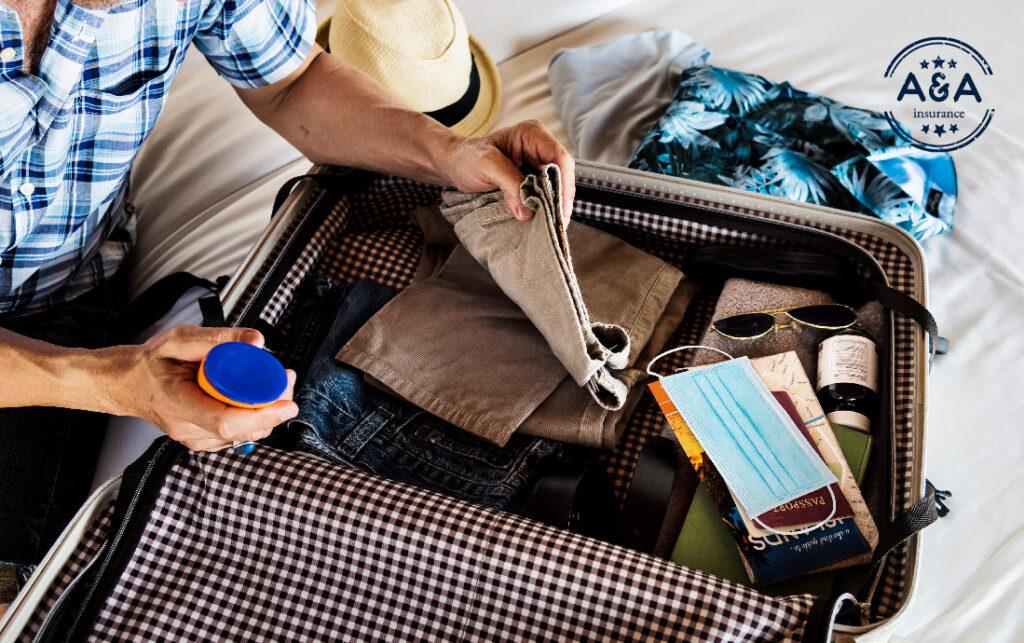 una persona arreglando su maleta en la que hay pantalones, camisas,, tapabocas, gafas, preparándose para viajar